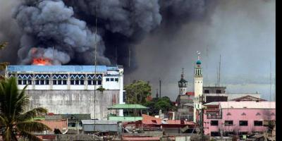 Marawi building set ablaze after Philippine airforce strike.