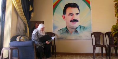 A volunteer at a women's centre in Qamişlo checks her register book by a portrait of Abdullah Öcalan.
