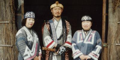 Three Ainu with traditional clothes.