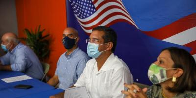 NPP gubernatorial candidate Pedro Pierluisi speaks during the election campaing; behind him a US flag.